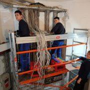 Auszubildende zum Ausbildungsberuf des Elektronikers beim auflegen der Klemmleiste der neuen Gebäudehauptverteilung