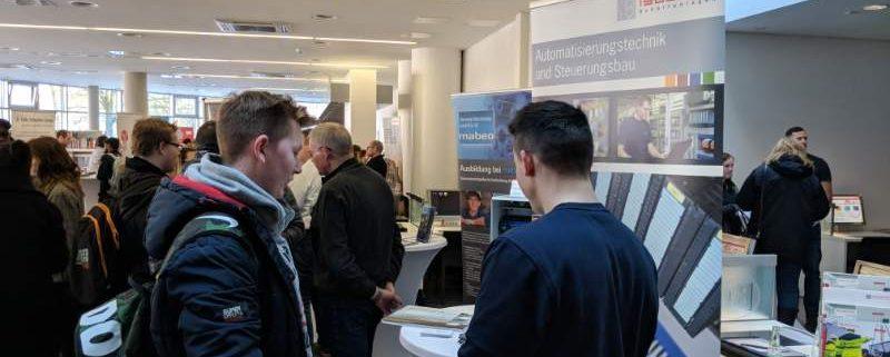 Lehrling der Firma Isoblock erklärt einem Besucher die Tätigkeiten eines Elektronikers